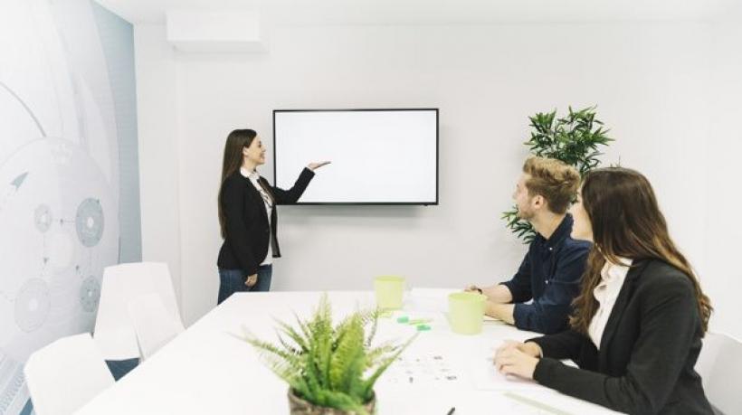 joven-empresaria-dando-presentacion-a-sus-colegas-en-reunion-de-negocios_23-2147826515